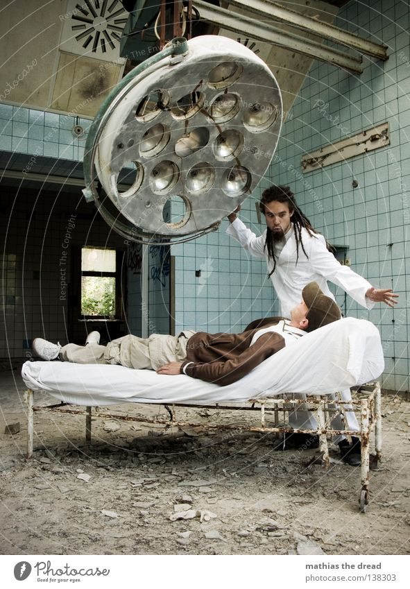 HYPNOSE Arzt Besteck Werkzeug weiß Schürze Rastalocken Operation Haare & Frisuren verfallen Krieg Zerstörung Müll Bauschutt Putz kaputt kurz klein Patient