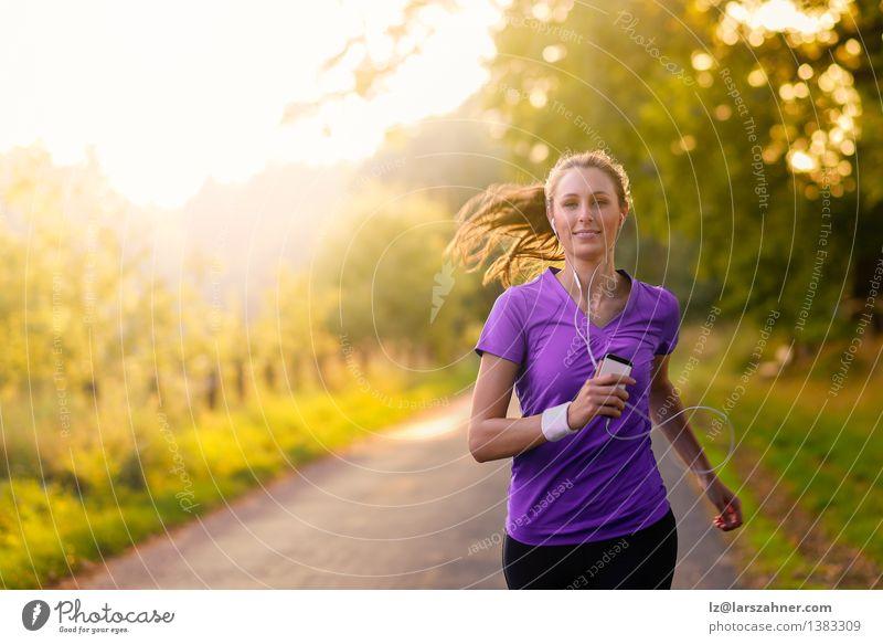 Frau, die Musik beim Joggen auf einer Straße hört Lifestyle Glück Sommer Sport Erwachsene Landschaft Herbst Baum Blatt Park T-Shirt Bewegung Fitness hören
