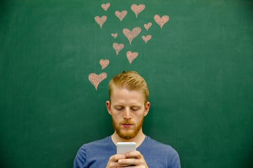 junger mann schreibt nachricht nutzt handy herzen Schule Tafel Studium lernen Student Kreide Handy PDA SMS Information Mensch maskulin Junger Mann Jugendliche