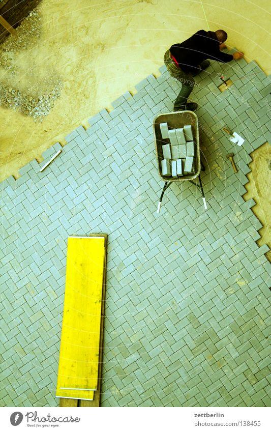 Bauwerk {n} = building Mann Arbeit & Erwerbstätigkeit Baustelle Arbeiter Gipfel Handwerk Verkehrswege Straßenbelag Bauarbeiter Pflastersteine Bergsteiger