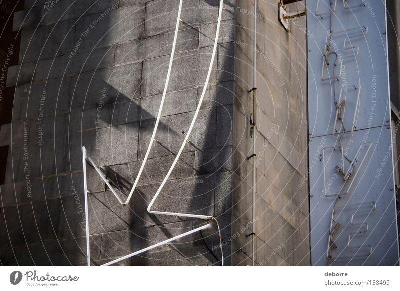 Nahaufnahme oder ein fluoreszierender Pfeil und Schild an der Seite eines Gebäudes. Leuchtreklame Neonlicht Wand Haus Detailaufnahme Werbung Hinweisschild Licht