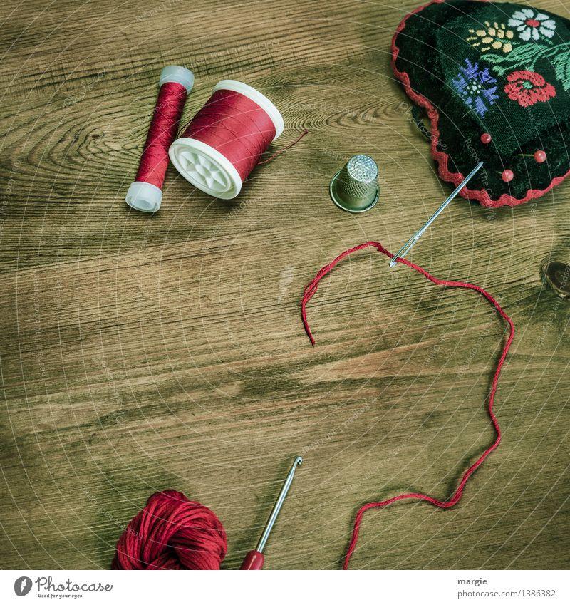 Rot eingefädelt: Nähzeug, wie Nadel, Garn, Fingerhut Wolle, Häkelnadel und ein Nadelkissen auf einem Holztisch Freizeit & Hobby Handarbeit stricken