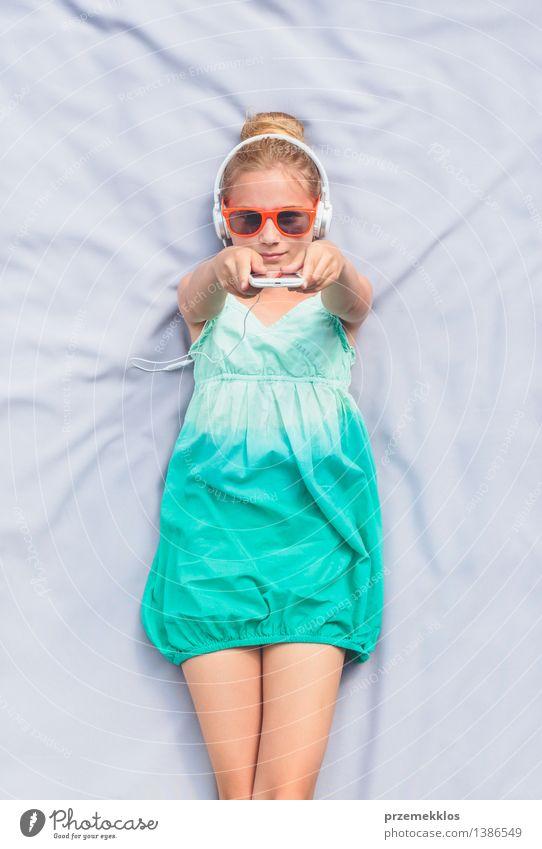 Mädchen, das auf einer Decke liegt und Musik hört Lifestyle Erholung Sommer Kind Telefon Mensch 1 8-13 Jahre Kindheit Kleid Sonnenbrille blond hören authentisch