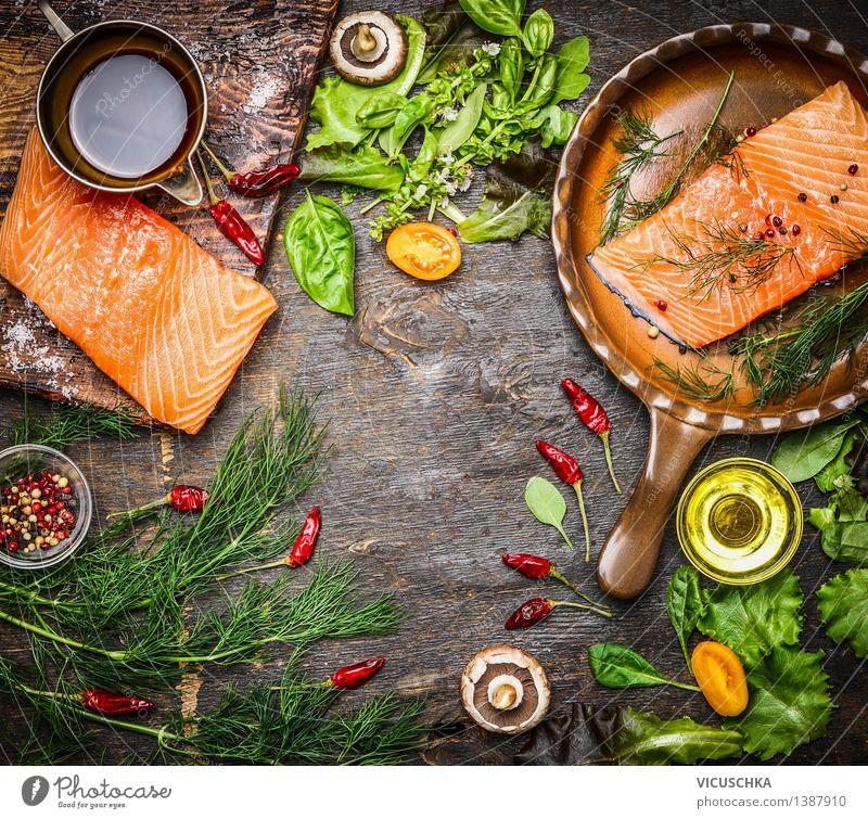 Lachsfilet auf rustikalem Küchentisch mit frischen Zutaten Lebensmittel Fisch Gemüse Salat Salatbeilage Kräuter & Gewürze Öl Ernährung Mittagessen Abendessen