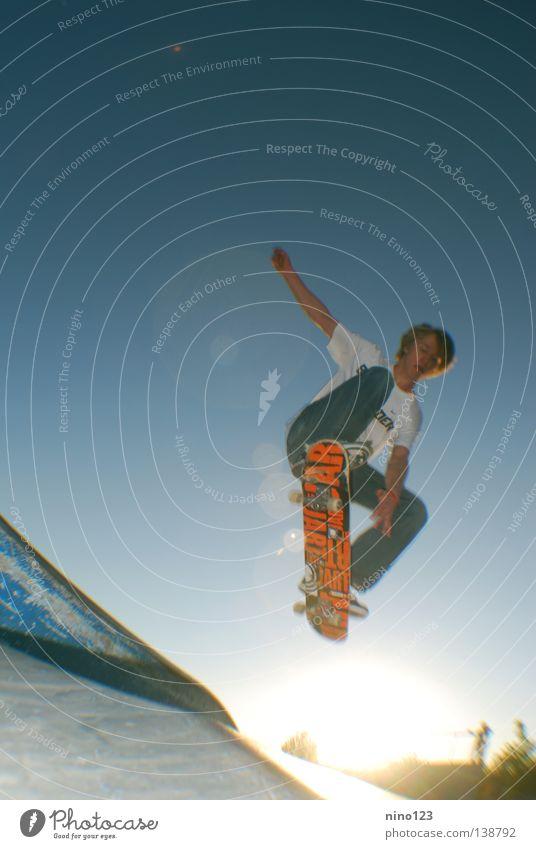 Grab Trick Stil Sport Spielen Funsport Sommer Leonidas Sonne blau Himmel Skateboarding orange Coolness