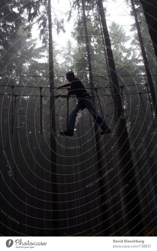 Cliffhanger Freude Spielen Sport Seil Mensch Mann Erwachsene Arme Hand Beine Baum Wald T-Shirt Hose Schuhe fangen festhalten gehen dunkel hoch schwarz