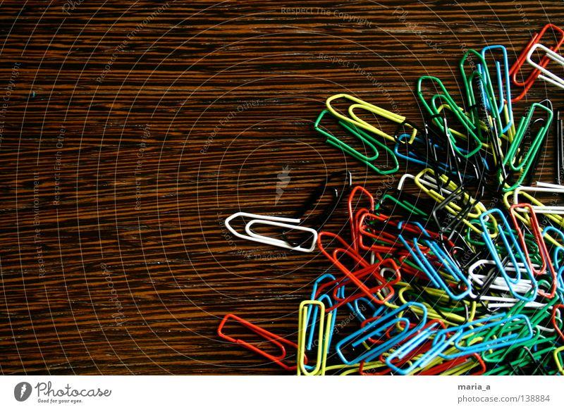 klammerkrams l Büroklammern chaotisch durcheinander mehrfarbig Holz gelb weiß rot-schwarz grün beweglich Draht Zusammenhalt Büroklammerchaos Maserung