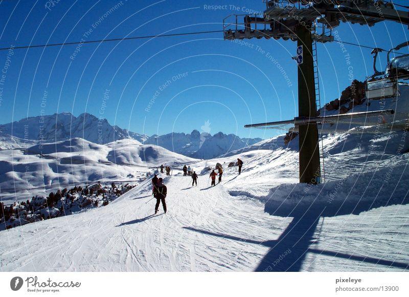 Skigruppe Sport Skifahren Mensch Schnee Berge u. Gebirge Himmel Abfahrt Talfahrt Skipiste Skilift Sesselbahn Mast Rolle Blauer Himmel abwärts Außenaufnahme