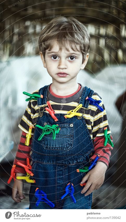 boy Kind blond Streifen T-Shirt Kleinkind child sad sadness play playful hair blue Jeanshose clamp toy childhood face eyes Caucasian looking serious standing