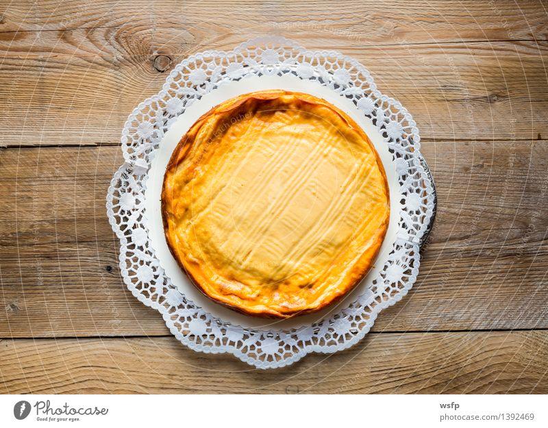 Käsekuchen auf rustikal Holz mit Tortenspitze Kuchen Dessert gelb Quarkkuchen Quarktorte Backwaren Biskuit Holztisch Landhaus Vogelperspektive süß Süßwaren rund