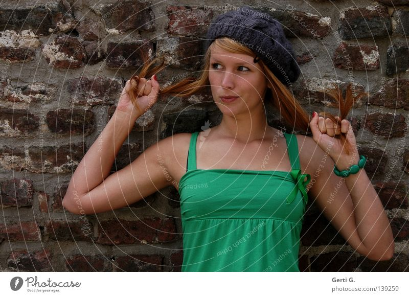 und was jetzt? Frau Junge Frau schön grün langhaarig rothaarig Mütze T-Shirt Gesichtsausdruck Hand Armband Mauer Wand Grimasse unentschlossen festhalten Porträt