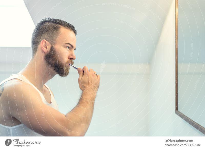 Junger bärtiger Mann, der seine Zähne putzt Gesicht Erwachsene Gesundheitswesen modern Sauberkeit Bad Spiegel Vollbart Zahnbürste dental Zahncreme mündlich
