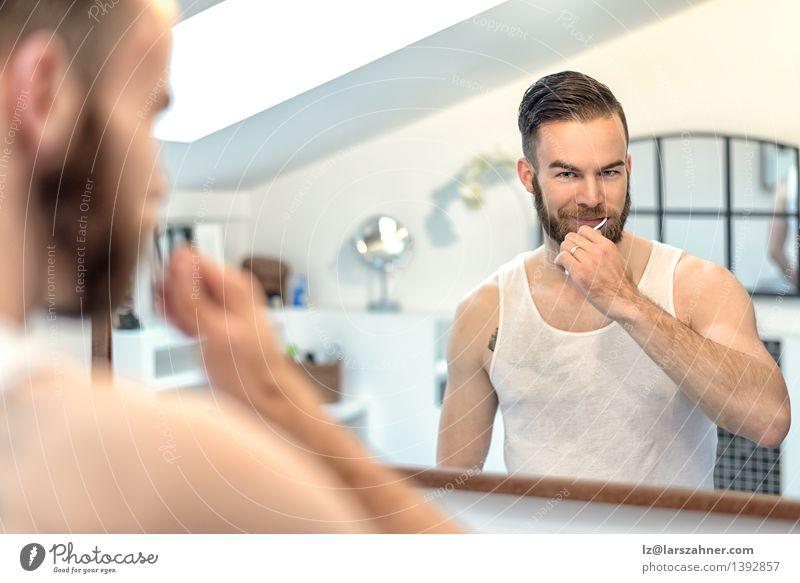 Sitzende Zähne des bärtigen Mannes im Badezimmer Gesicht Erwachsene Gesundheitswesen modern Sauberkeit Spiegel Vollbart Zahnbürste dental Zahncreme mündlich