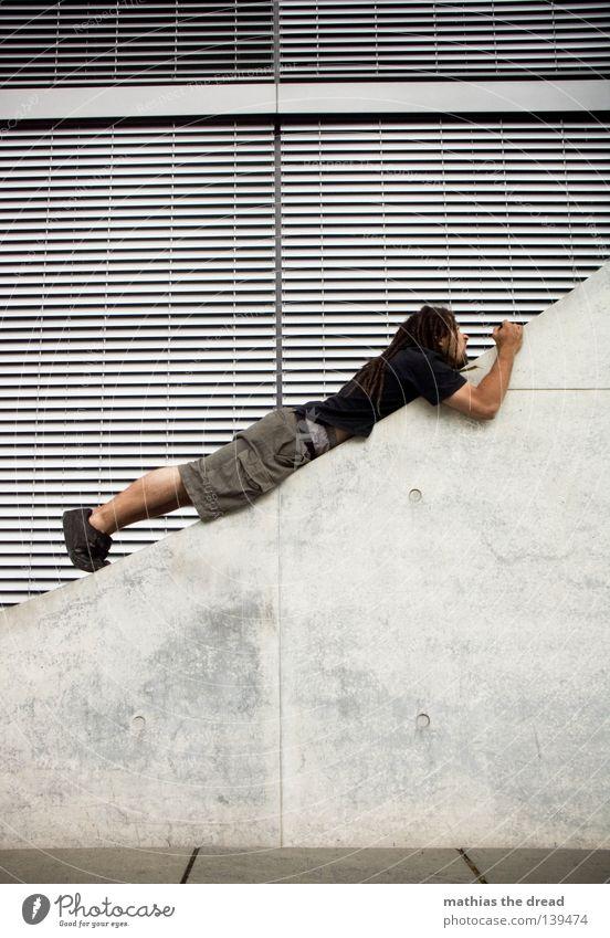 BLN 08 | STEIL HINAUF Architektur Fassade Beton liegen diagonal aufwärts Neigung steil Junger Mann streben ausgestreckt Le Parkour Jalousie Steigung Betonwand