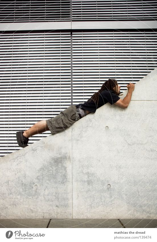 BLN 08 | STEIL HINAUF Architektur Fassade Beton liegen diagonal aufwärts Neigung steil Junger Mann streben ausgestreckt Le Parkour Jalousie Steigung Betonwand Betonmauer