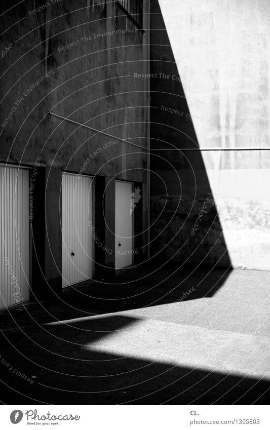 hinterhof Platz Mauer Wand Garage Garagentor dunkel eckig trist parken Parkplatz Hinterhof Schattenspiel Schwarzweißfoto Außenaufnahme Menschenleer Tag Licht