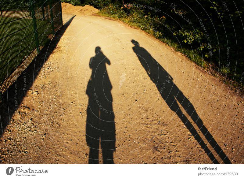 Die Geschichte der Ungleicheit einer Freundschaft Licht Zaun lang dunkel Silhouette Umrisslinie lang gezogen Am Rand Zusammensein wandern groß klein dünn Sommer