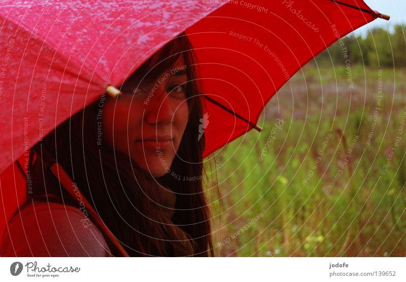 Bln 08 | es regnet... Frau Jugendliche feminin Lebewesen Regenschirm nass feucht schlechtes Wetter Freundlichkeit sympathisch Wiese Gras Brachland grün rot