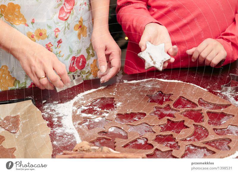 Die Weihnachtssymbole im Teig für die Plätzchen herausschneiden Tisch Küche Mensch Mädchen Frau Erwachsene Hand 2 8-13 Jahre Kind Kindheit 30-45 Jahre machen