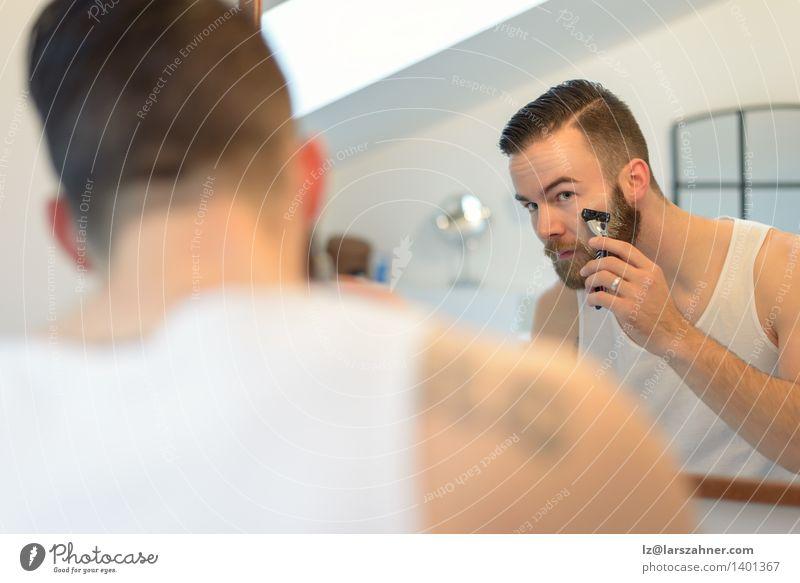 Junger Mann, der über seinem Bart sich rasiert Gesicht Spiegel Bad Erwachsene Vollbart Sauberkeit Präzision Vorschein Pflege Kaukasier Wange konzentrierend
