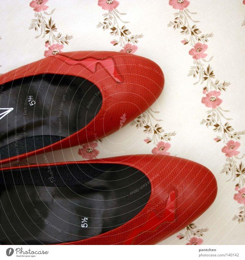 Rote Schuhe mit einer Blitz applikation liegen auf einer geblümten Tapete. Ausgehen, Diskothek, tanzen. Retro ausgehen Mode Bekleidung Leder Damenschuhe Kitsch