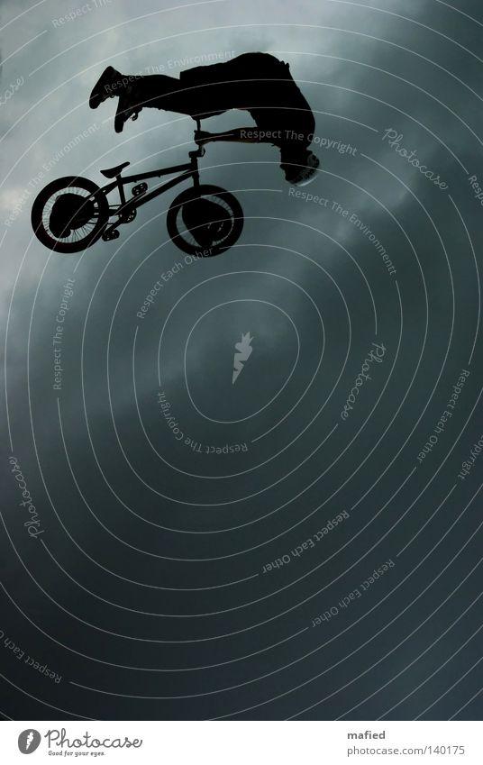 Absteiger Fahrrad Reifen Rad BMX springen Rampe Akrobatik kopfvoran Abstieg fliegen Himmel Wolken dunkel Gegenlicht schwarz weiß grau blau Extremsport move