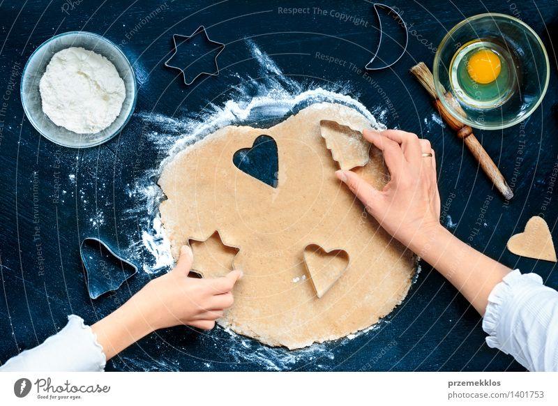 Mutter mit der Tochter, welche die Weihnachtssymbole im Teig ausschneidet Tisch Küche Mensch Mädchen Frau Erwachsene Hand machen geschnitten Teppichmesser Ei