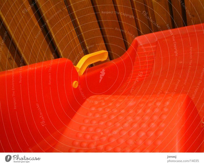Mit dem Bob unterwegs... Schlitten rot Holz Noppe gelb Freizeit & Hobby Plastikbob Schnee Balken Detailaufnahme Griff Bremse Holzbrett Holzwand Kellerwand