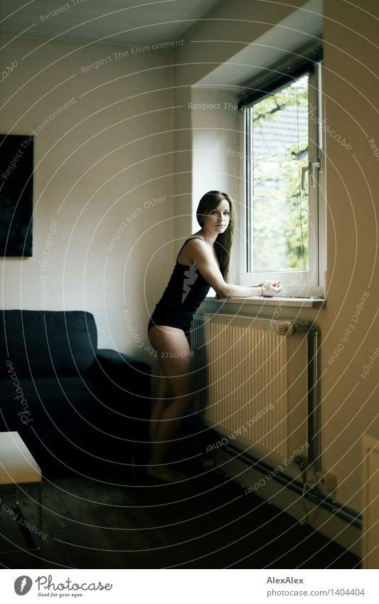junge Frau in schwarzem Body steht am Fenster und schaut in die Kamera sportlich Wohlgefühl Zufriedenheit Junge Frau Jugendliche Beine 18-30 Jahre Erwachsene