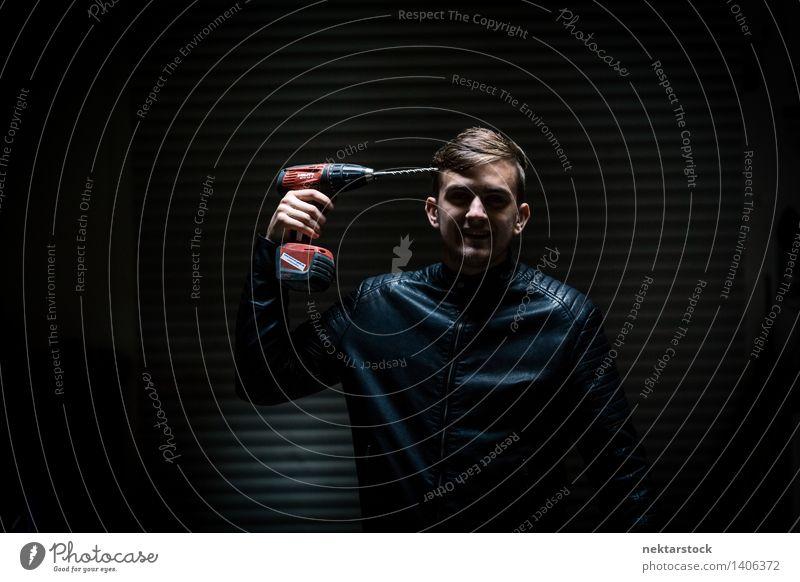 man with electric screwdriver in dark garage schön Mensch maskulin Junger Mann Jugendliche Körper 1 13-18 Jahre Aggression rot schwarz Gefühle Ehre Wut