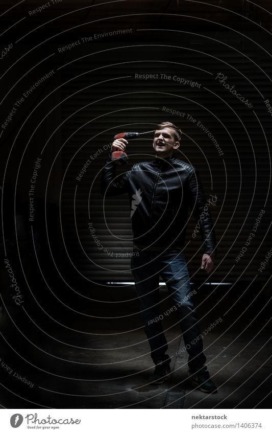 man with electric screwdriver in dark garage schön Mensch maskulin Junger Mann Jugendliche Körper 1 13-18 Jahre Aggression Wut rot schwarz Macht Mut Ärger
