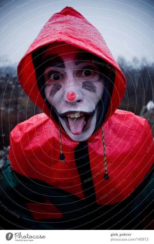 Verrückter Clown. Porträt Mann Zähne Straße Müll Nase Bekleidung Sibirien Luft Kapuze Kopf Hut Freude grimmig Männer gedacht Regen rot dunkel Kapuzenpulli
