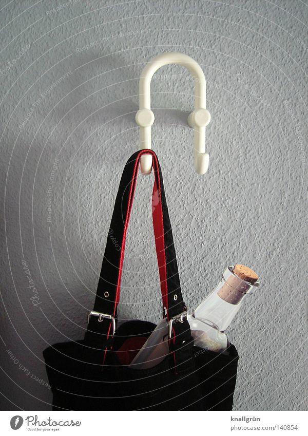 Flasche in Tasche Glasbehälter Korken Flaschenpost hängen Haken Kleiderständer weiß grau schwarz rot hell Schatten Schnalle Raufasertapete Wand obskur Flur