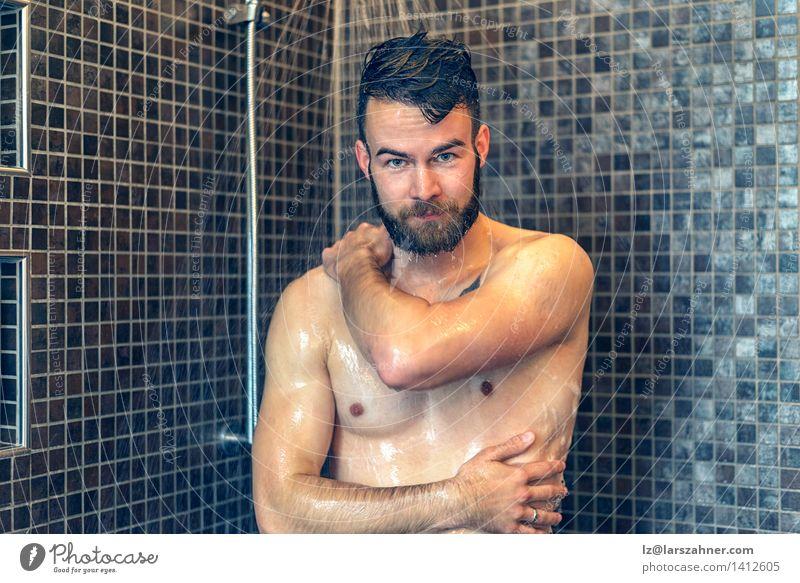 Freundlicher junger Mann, der unter der Dusche sich einseift Haut Gesicht Wellness Bad Erwachsene Vollbart Lächeln nass Sauberkeit vor der Kamera Baden Pflege