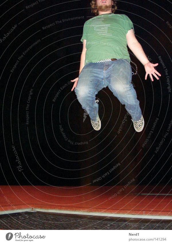 Jump rot springen Trampolin Jeansstoff Mann Bart Hand grün Nacht schwarz Freude anstrengen Hose Beine Finger T-Shirt dunkel hüpfen Bewegungsenergie Schwerkraft