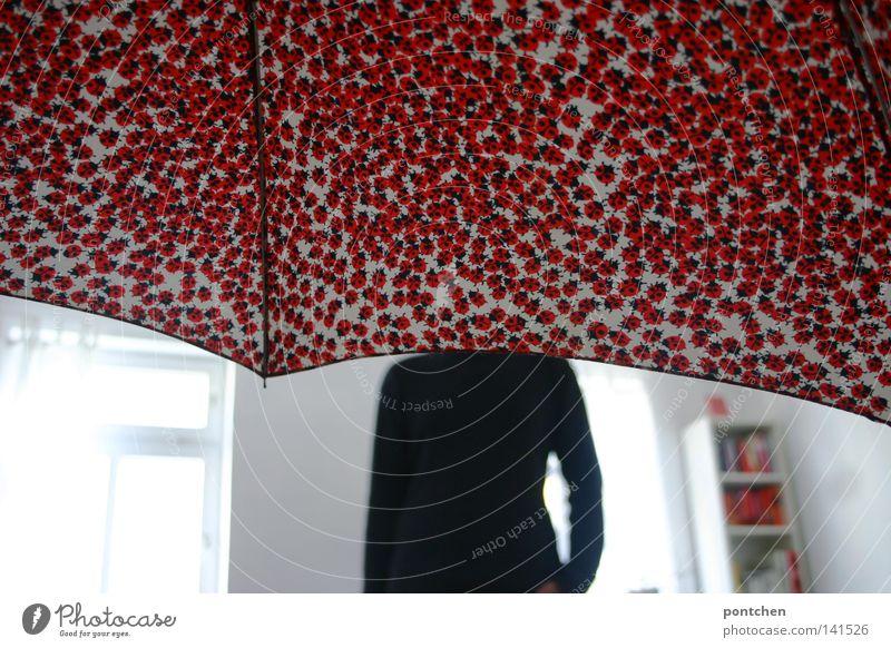 Kopflos. Mann steht in einem hellen zimmer. Sein Kopf wird von einem Regenschirm verdeckt. Verstecken Marienkäfer Raum weiß Licht Regal verstecken Wohnung rot