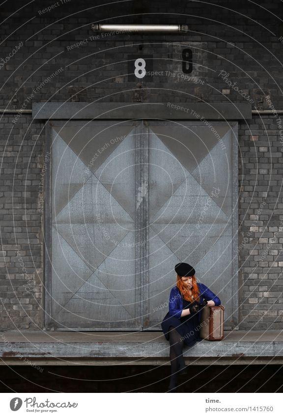 Anastasia feminin 1 Mensch Industrieanlage Bauwerk Gebäude Lagerhalle Mauer Wand Deckenlampe Rampe Kleid Jacke Koffer Handschuhe Mütze rothaarig langhaarig