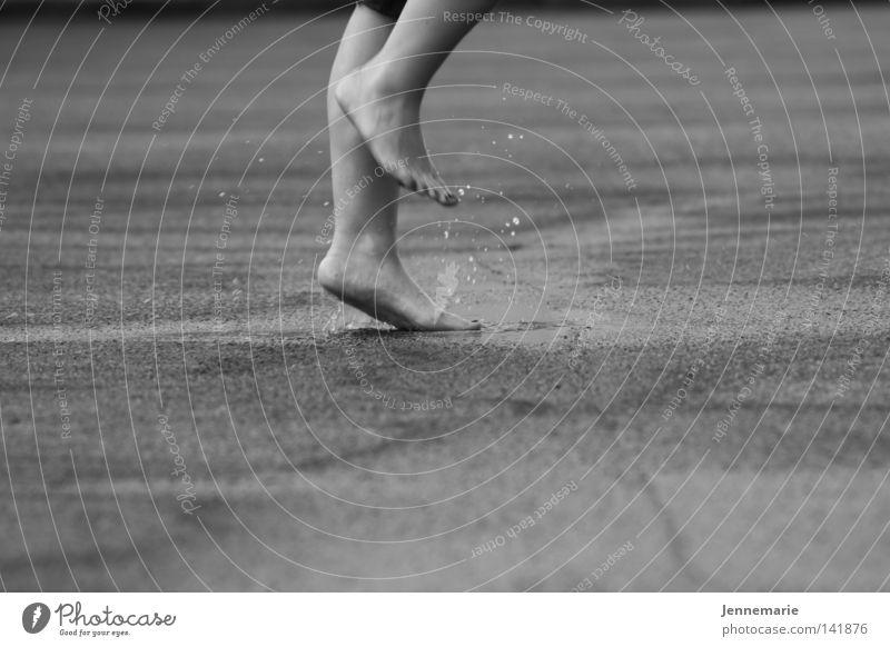 pitsche patsche nass Asphalt Regen Schwarzweißfoto Fuß Beine fütze spritzen Wassertropfen