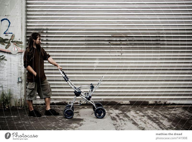 BLN 08 | SCHON MAL ÜBEN 1 Mensch einzeln Ein junger erwachsener Mann Erwachsene 30-45 Jahre Außenaufnahme Rolltor Kinderwagen Ganzkörperaufnahme