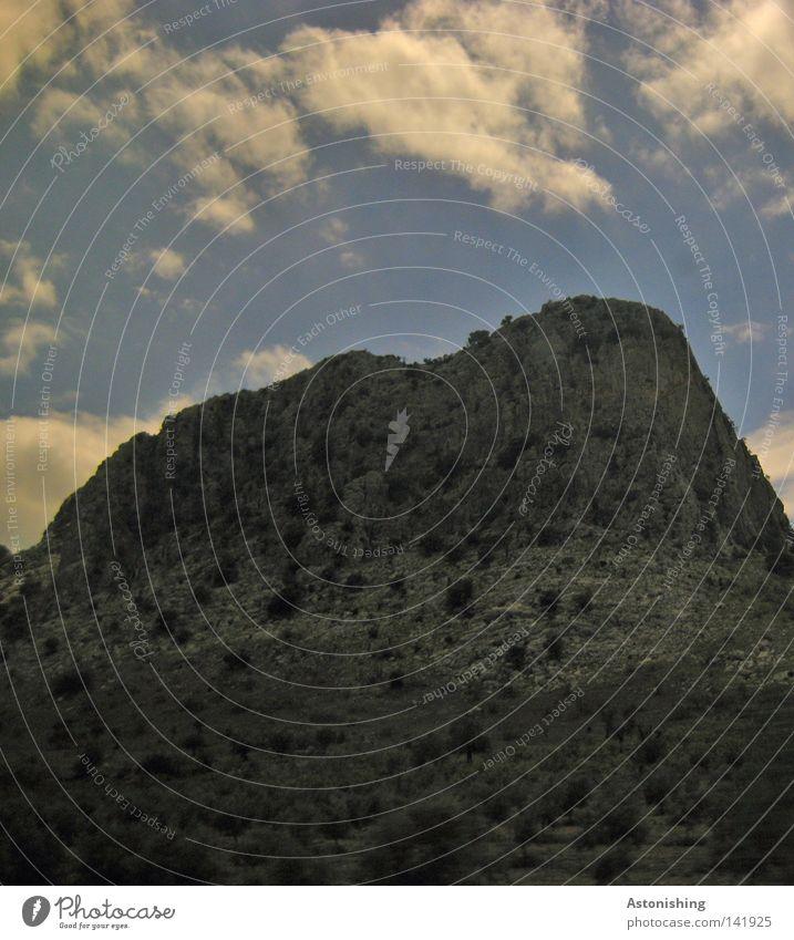 The Rock Berge u. Gebirge Pflanze Himmel Wolken Felsen Stein dunkel grau Spanien Kontrast steil Steilwand Menschenleer Landschaft Wolkenhimmel karg