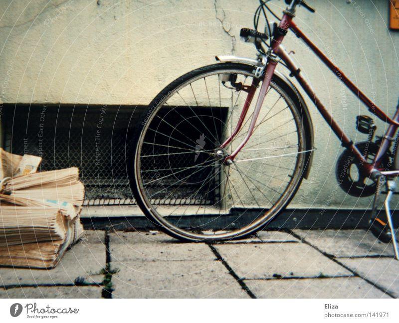 liegengelassen Bürgersteig Fahrrad Zeitung alt vergilbt Reifen Speichen Gitter Wand fließen Haus parken Zeitschrift Ausschnitt. Kellerfenster absetzen