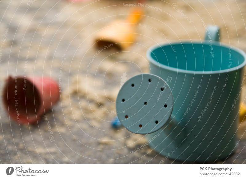 sandplatzspiele Sandkasten Gießkanne Schaufel Eimer Kübel Makroaufnahme blau gelb rot Nahaufnahme