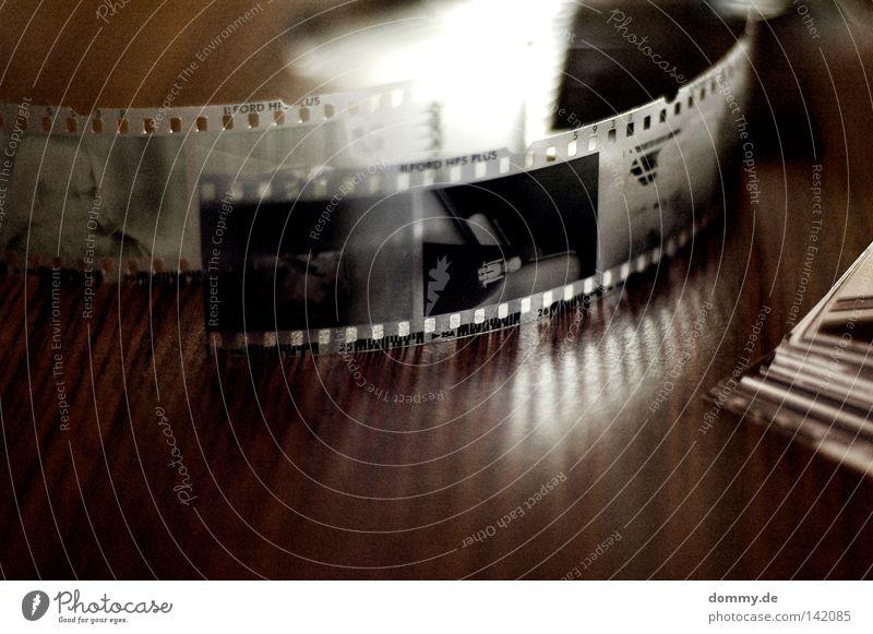 abgelehnt! negativ Streifen schwarz weiß Rolle Filmmaterial Holz Tisch dunkel Licht Blick Loch Papier analog old-school Suche erfassen Makroaufnahme Nahaufnahme
