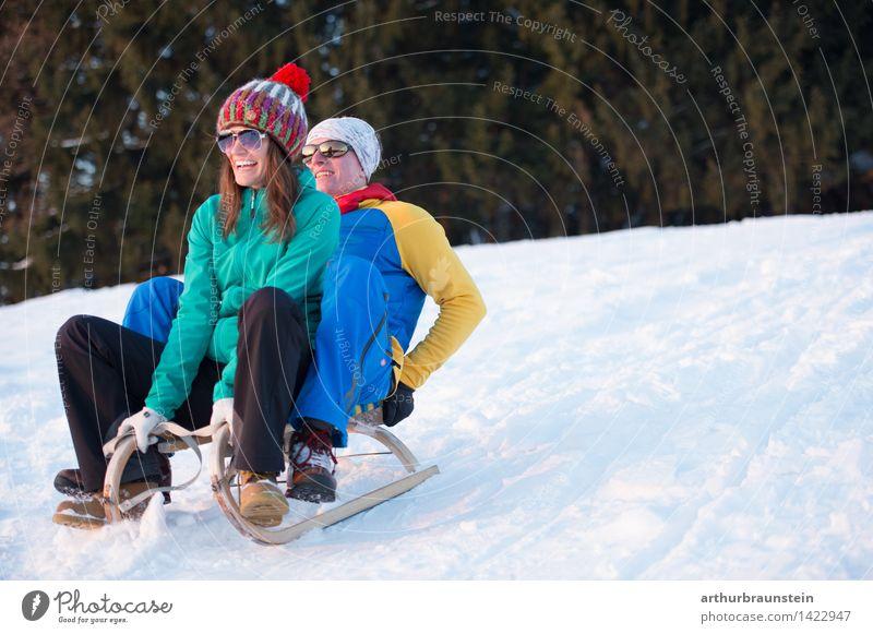 Junges Paar beim Schlittenfahren Freude Freizeit & Hobby Winter Schnee Winterurlaub Wintersport Skipiste Mensch maskulin feminin Junge Frau Jugendliche