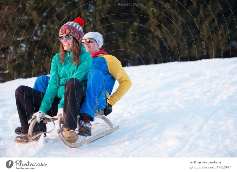 Junges Paar beim Schlittenfahren Mensch Natur Jugendliche Junge Frau Junger Mann Freude Winter Wald kalt Erwachsene Leben Bewegung Schnee feminin Freundschaft