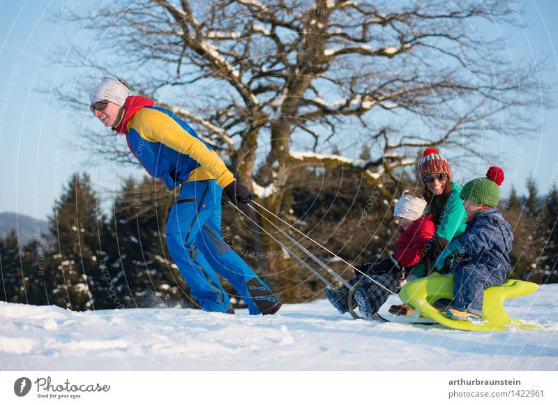 Junges sportliches Paar mit Kindern am Schlitten im Winter bei Sonnenschein Freude Freizeit & Hobby Ferien & Urlaub & Reisen Tourismus Winterurlaub Wintersport