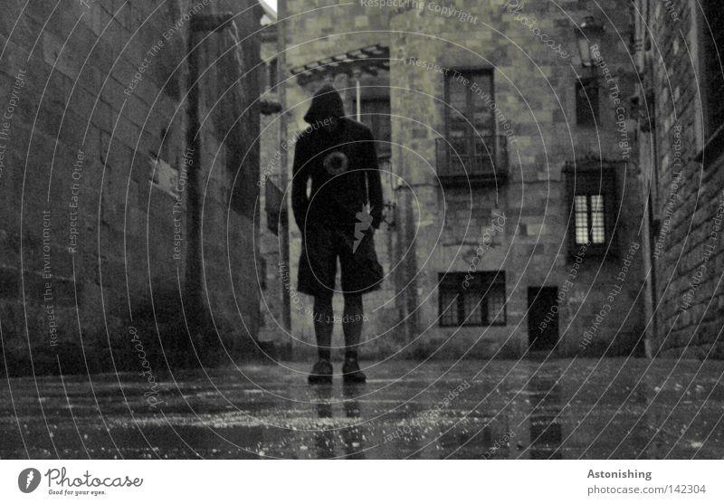dunkler Mann in dunkler Gasse Stadt Haus Straße dunkel Fenster grau Stein Mauer Regen gefährlich stehen Boden bedrohlich Barcelona