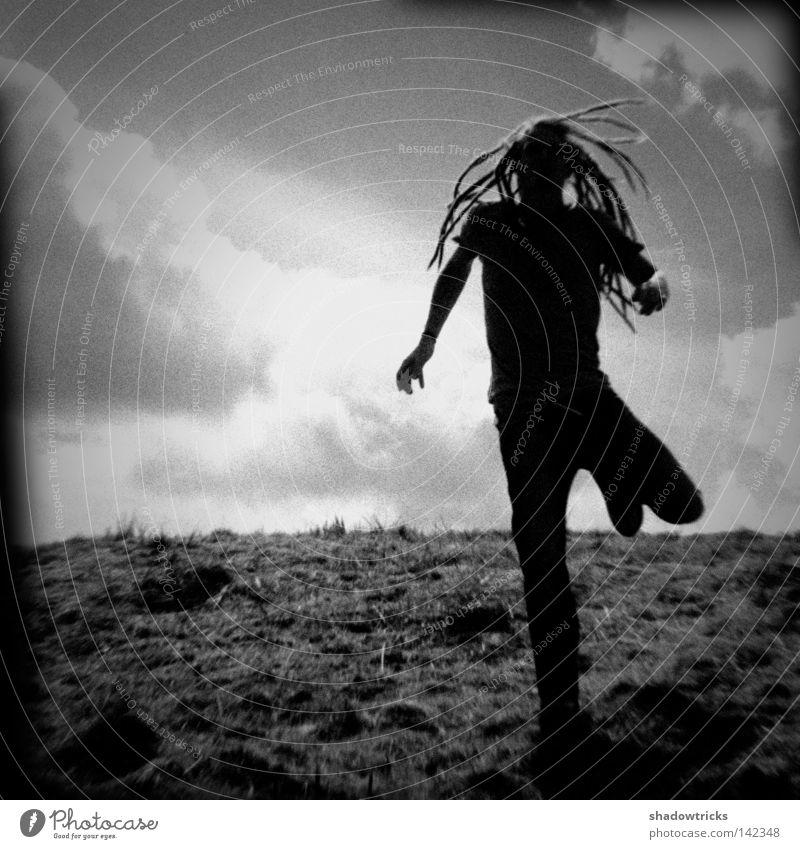 Flucht Gegenlicht Rastalocken Holga Wiese alt Zwanziger Jahre Wolken grau schwarz weiß laufen gehen oben Mensch Berge u. Gebirge Schwarzweis Kontrast Backlicht