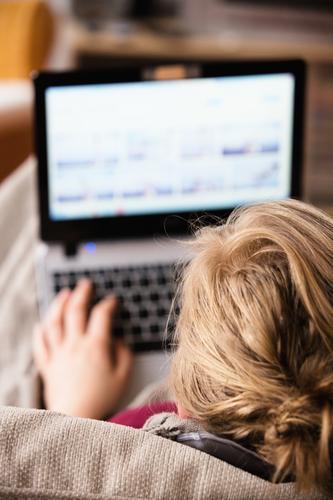 Junge Frau, Schülerin am laptop, . Homeschooling, Homeoffice Wohnung Sofa Wohnzimmer Notebook lernen Bildschirm Unterhaltungselektronik feminin blond