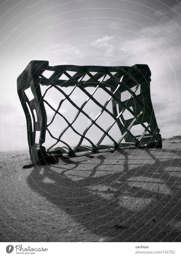 Strandschönheit Sandkorn körnig Strandgut Umweltverschmutzung Kiste Gegenlicht blenden Sylt Küste Schwarzweißfoto obskur hochkant angeschwemmt